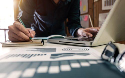 """uma pessoa trabalhando no computador e escrevendo em uma caderneta, representando a atribulada vida de quem quer """"fazer acontecer"""""""