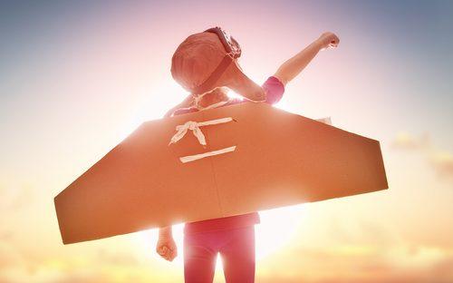 uma criança com asas de papelão nas costas, como quem sonha em voar.