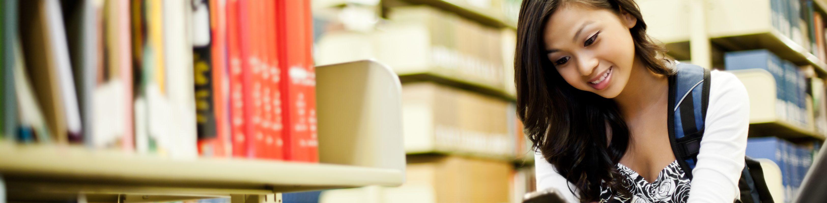 uma jovem lendo no celular em uma biblioteca