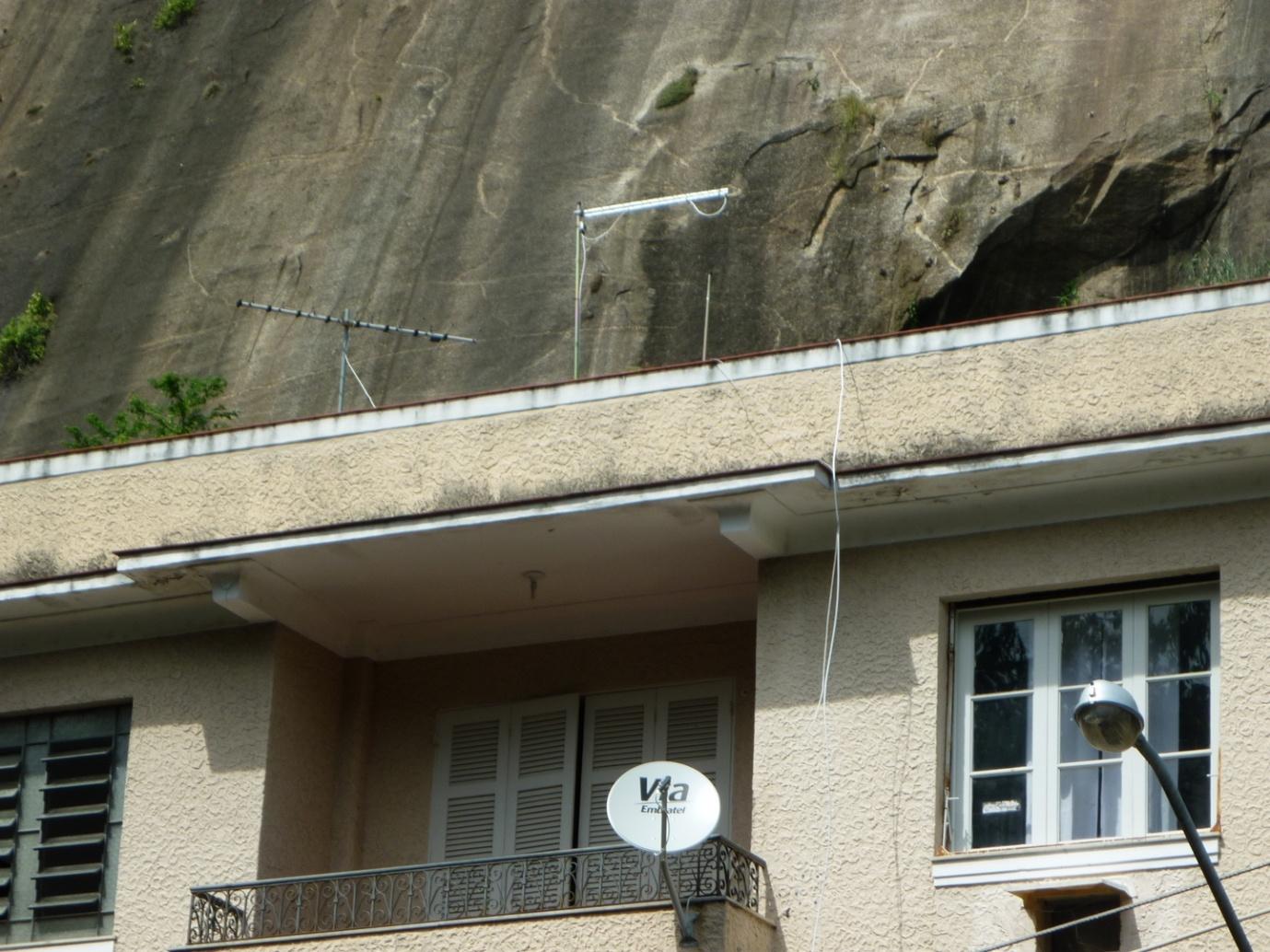 Uma antena UHF solitária, em uso para DTV, próxima de outra, VHF, abandonada. No apartamento de baixo, a situação de quem vive em locais sem sinal analógico de televisão, dentro da área urbana da cidade.